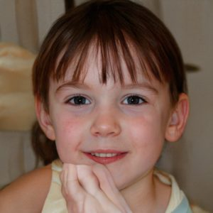 A young girl looks directly at the camera, smiling. A fleshy appendage is close to her chin.